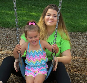 Conklin Summer Fun student with young girl on swing